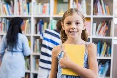 拿着一本书的女孩在图书馆里 免版税库存照片