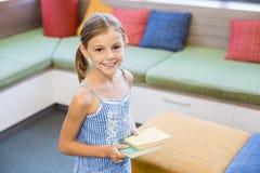 拿着一本书的女孩在图书馆里 免版税库存图片