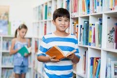 拿着一本书的男孩在图书馆里 库存照片