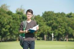 拿着一本开放书的英俊的男孩,读了背景夏天绿色 免版税图库摄影