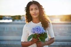 拿着一朵俏丽的花的可爱的妇女 免版税图库摄影
