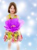 拿着一朵大紫色花的小女孩 库存图片