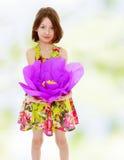 拿着一朵大紫色花的小女孩 免版税库存图片
