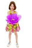 拿着一朵大紫色花的小女孩 库存照片