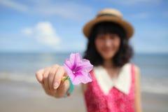 拿着一朵桃红色花的秀丽 免版税库存图片