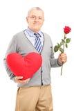 拿着一朵红色心脏和花的成熟绅士 图库摄影