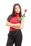 拿着一朵红色玫瑰的美丽的沉思妇女 免版税图库摄影