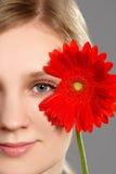 拿着一朵红色花的一名聪慧的妇女的画象 免版税库存照片