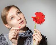 拿着一朵红色花的一名聪慧的妇女的画象 库存照片
