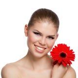 拿着一朵红色花的愉快的微笑的年轻白种人妇女画象  库存图片