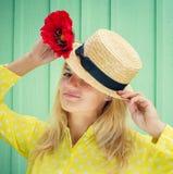 拿着一朵红色花的草帽的美丽的白肤金发的妇女 免版税库存图片