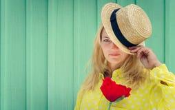 拿着一朵红色花的草帽的美丽的白肤金发的妇女 免版税库存照片