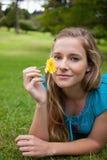 拿着一朵黄色花的女孩,当在公园时 免版税图库摄影