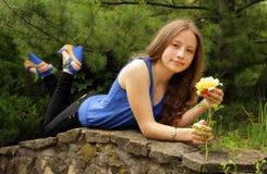 拿着一朵黄色玫瑰的俏丽的女孩 库存图片