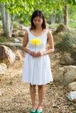 拿着一朵黄色花的亚裔妇女 免版税库存图片