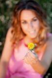 拿着一朵黄色花的妇女 库存照片