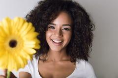 拿着一朵黄色花的微笑的妇女 免版税图库摄影