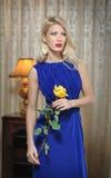 拿着一朵黄色花的长的典雅的蓝色礼服的年轻美丽的豪华妇女。有帷幕的美丽的年轻白肤金发的妇女 库存照片