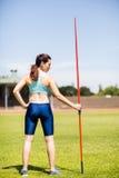 拿着一杆标枪的女运动员背面图在体育场内 免版税库存图片