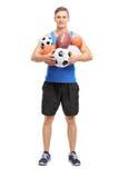 拿着一束不同的体育球的运动员 免版税库存图片