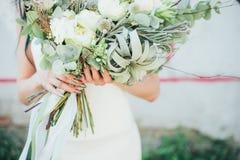拿着一束五颜六色的花的妇女在被伸出的手上 库存照片