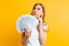 拿着一束在黄色背景的钞票的一个沉思哀伤的女孩的画象 免版税库存图片