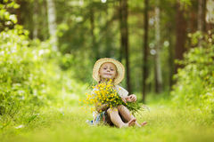 拿着一束巨大的花在晴朗的夏时的向日葵的领域的一个逗人喜爱的矮小的微笑的女孩 免版税库存照片