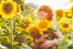 拿着一束巨大的花的向日葵的领域的年轻红发妇女在一个晴朗的夏天晚上 免版税库存照片