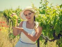拿着一束成熟葡萄的帽子的妇女在一个晴天 免版税库存图片
