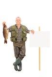 拿着一条大鱼的成熟渔夫在盘区旁边 库存照片