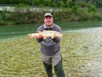 拿着一条新鲜的被抓的鱼的渔夫 免版税库存图片