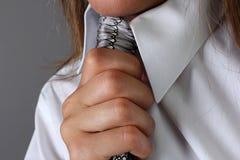 拿着一条灰色领带的女性手 工作室 库存照片