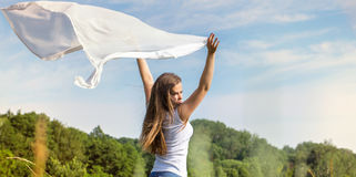 拿着一条白色围巾的美丽的妇女 免版税库存照片