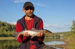 拿着一条美丽的三文鱼的渔夫 库存图片