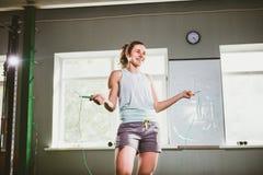 拿着一条跨越横线的年轻白种人微笑的妇女-健康和健身概念 库存照片