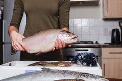 拿着一条鳟鱼的少妇在她的厨房里 库存照片