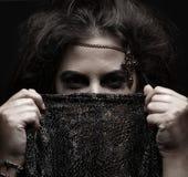 拿着一条黑暗的围巾的阿拉伯妇女的纵向 库存照片