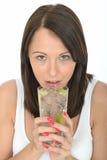 拿着一杯与被切的石灰的被冰的水的可爱的健康自然少妇 免版税库存图片