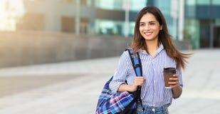 拿着一杯咖啡与一个背包的年轻微笑的妇女在她的肩膀 r 免版税库存图片