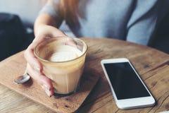 拿着一杯咖啡与巧妙的电话的妇女` s手在咖啡馆的木桌上 库存照片