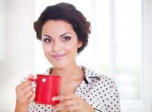 拿着一杯咖啡佩带的睡衣的愉快的妇女 免版税图库摄影
