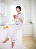 拿着一杯咖啡佩带的睡衣的愉快的妇女 免版税库存照片