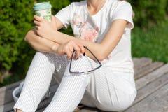 拿着一杯咖啡和太阳镜的女孩在腿有现代时兴的镶边裤子的 免版税库存图片