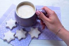 拿着一杯咖啡和曲奇饼的手在一个白色木桌特写镜头 免版税库存照片