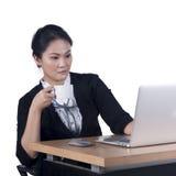 拿着一杯咖啡和查看膝上型计算机scr的女商人 库存图片
