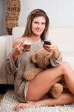 拿着一杯咖啡和遥控的女孩 库存图片