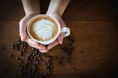 拿着一杯咖啡在一张老木桌上的,顶视图的妇女手 库存照片