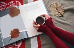 拿着一杯咖啡在书的妇女的手 免版税库存图片