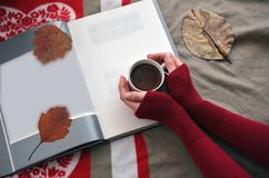 拿着一杯咖啡在书的妇女的手 图库摄影