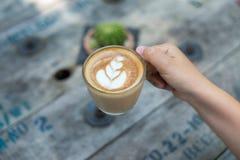 拿着一杯咖啡在木桌,顶视图的女性手 库存图片